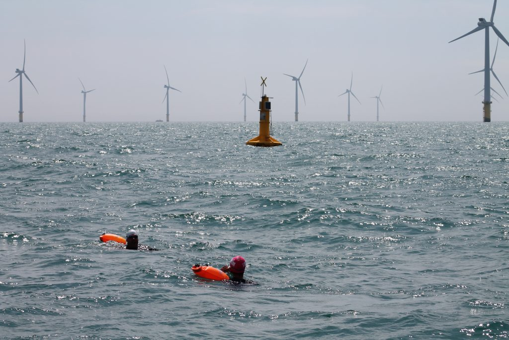 Swimmers at the start line, with the Rampion North Marker and windfarm in background.