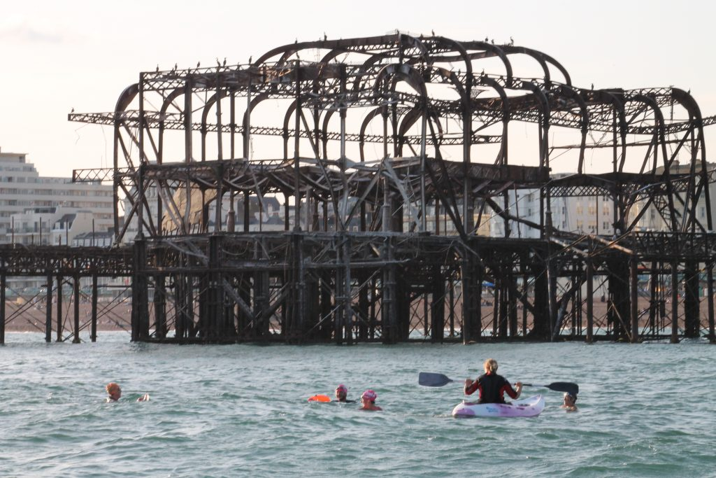 Swimmers with Kayak approaching West Pier at Brighton